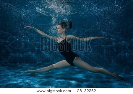 The woman dances at the bottom under water she is surrounded by bubbles.