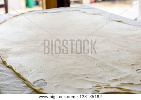Homemade Phyllo or strudel dough on a home table cloth ready for apple strudel baklava burek pie or other kind of traditional pastry. poster