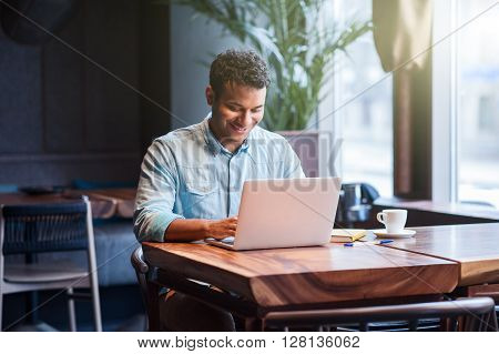 Handsome young Arabian man is typing on a laptop in cafe. He is sitting at desk and smiling