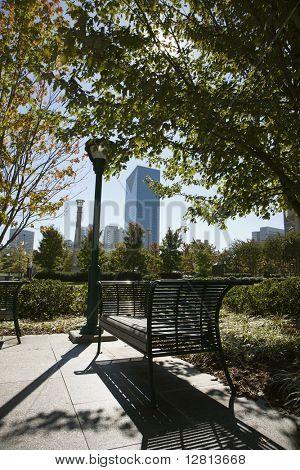 Empty bench in urban park in Atlanta, Georgia with buildings in background.