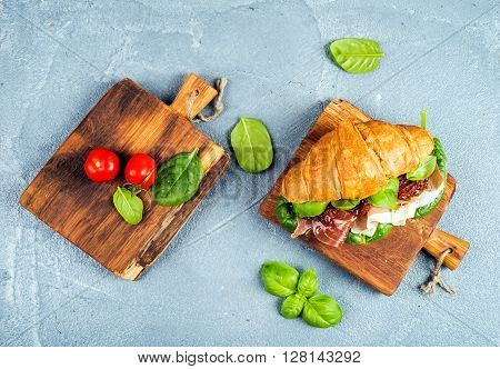 Croissant sandwich with smoked meat Prosciutto di Parma, sun dried tomatoes, fresh spinach and basil on small rustic wooden boards over stone textured grey background, top view