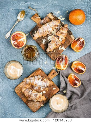 Traditional Italian style home breakfast. Latte in glasses, almond croissants on rustic wooden boards and red bloody Sicilian oranges over concrete textured table, top view