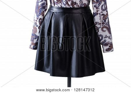 Skirt with folds and shirt. Black leather skirt with folds. Stylish skirt on display. Woman's new leather garment.