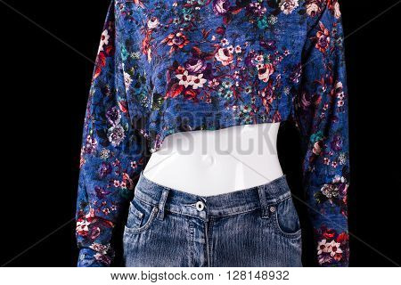 Crop top with floral pattern. Short blue top on mannequin. Woman's asymmetric top with print. Quality material and stylish pattern.