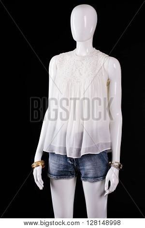 White top with denim shorts. White mannequin wearing summer top. Girl's brand new summer garment. Seasonal sale with discounts.