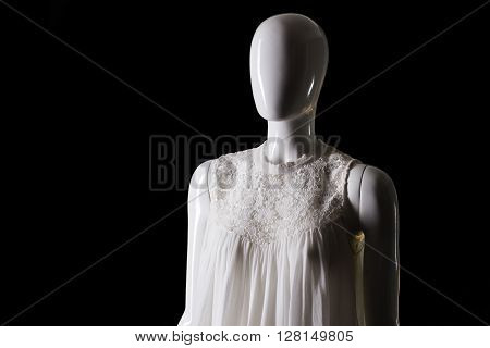 White sleeveless summer top. Mannequin wearing top with insert. Girl's stylish garment on sale. Delicate and beautiful clothing.