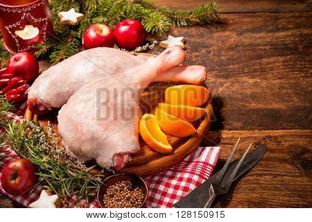 Raw goose legs with herbs on cutting board. Cooking at Christmas time