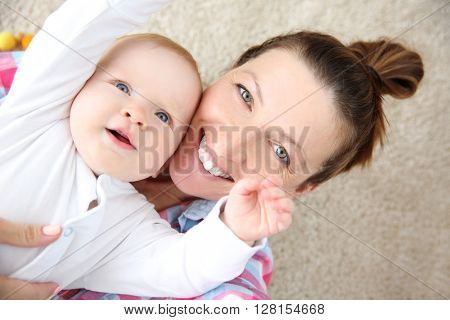 Young mother taking a selfie with her baby on the floor, close up