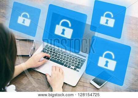 Woman working on laptop with icons security on virtual display. Technology, internet and networking concept.