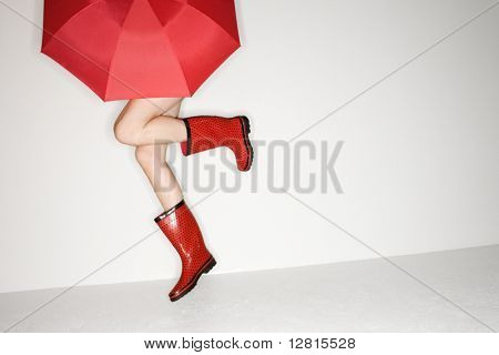 Legs of young Caucasian woman in red boots holding red umbrella and jumping.