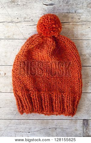 wool orange pompom hat closeup on wooden background