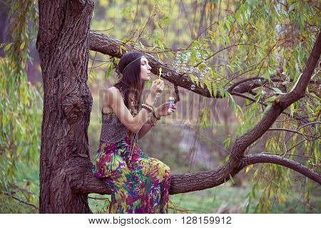 Hippie Girl on a tree branch blowing bubbles