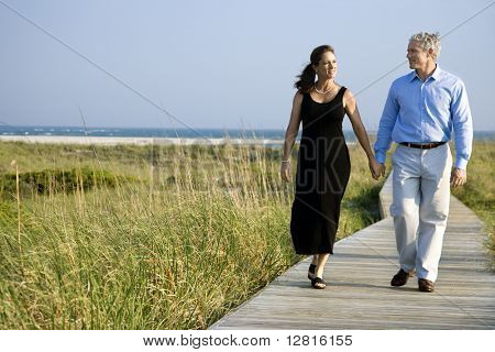 Caucasian mid-adult couple holding hands and walking on walkway.