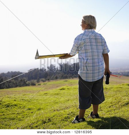 Pre-teen Caucasin male holding remote control and airplane standing on a grassy knoll.