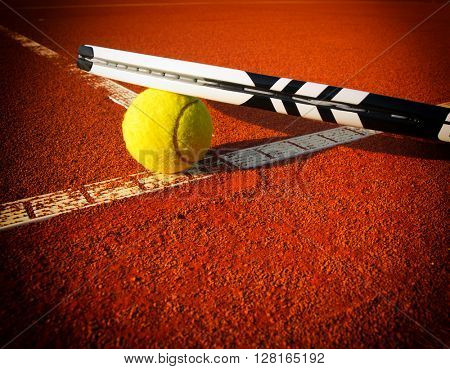 Tennis ball and racquet on a tennis clay court