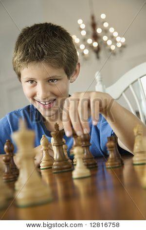Caucasian pre-teen boy playing chess.