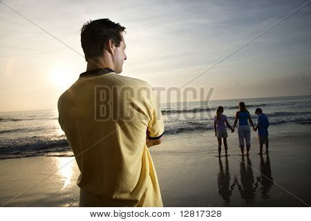 Caucasian mid-adult man standing and watching mid-adult woman with children on beach.