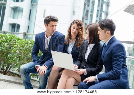 Business people sitting down outdoor and working otgether