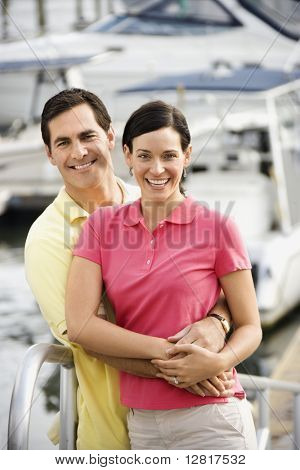Portrait of Caucasian mid-adult couple embracing at harbor.