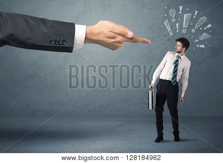 Employee in trouble getting last warning from boss concept with big business hand pointing at salesman and drawn exclamation marks