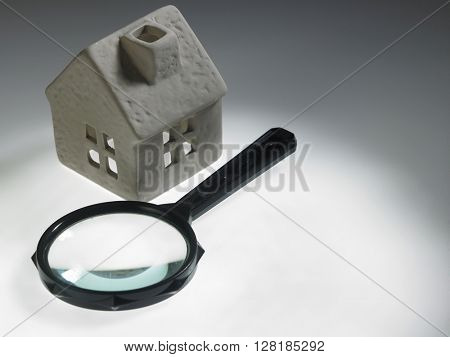 magnifying glass and house model isolated over white background