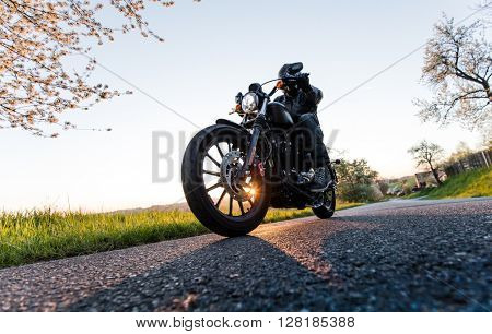 Man sat on motorcycle on the road during sunrise.