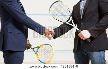 Two businessmen shaking hands before playing squash on court. Sporty men holding rackets on squash court.