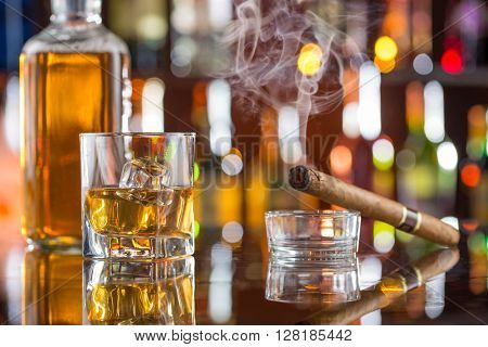 Whiskey drinks on bar counter with blur bottles on background.