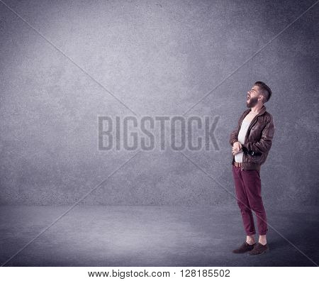 A hipster guy in stylish clothes shouting in front of an empty urban concrete wall background concept