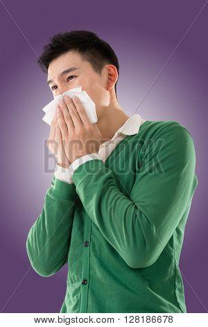 Sneezing asian man, closeup portrait.