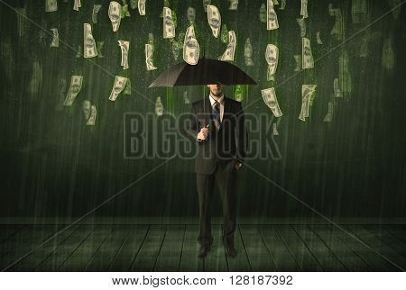 Businessman standing with umbrella in dollar bill rain concept on background