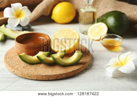 Still life with avocado oil on wooden table closeup