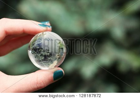 Female hand holding small glass globe closeup