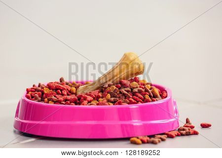 Pet food in a pink bowl on a floor.