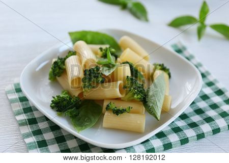 Boiled rigatoni pasta with broccoli and basil on white plate