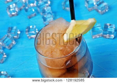 Glass of cola with crushed ice on blue wooden table