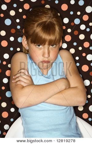 Caucasian female child pouting with arms crossed.