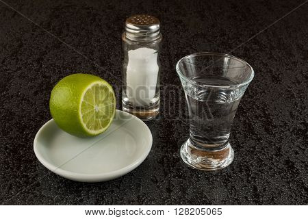 Silver tequila with lime on black background. Tequila shot. Silver mexican tequila. Alcohol drink