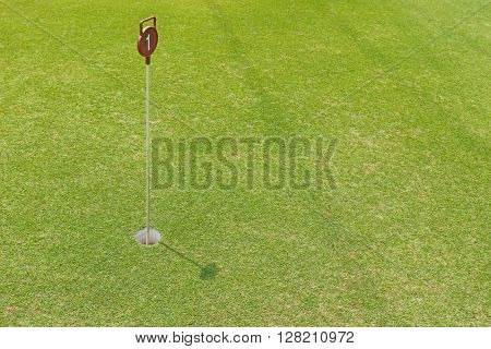 Soft focus of a hole at putting cup hold showing number one pin at outdoor practice putting green, sunny day