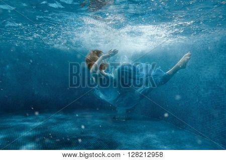 The girl from the fairy tale in a blue dress sinks under water.