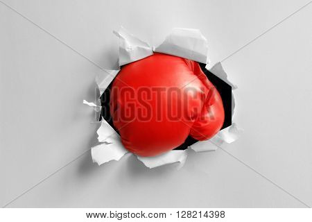 Boxing gloves knockout punch punching through torn paper hole ready for message on glove