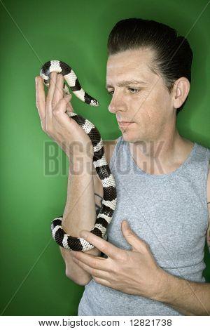 Caucasian mid-adult male holding California Kingsnake.