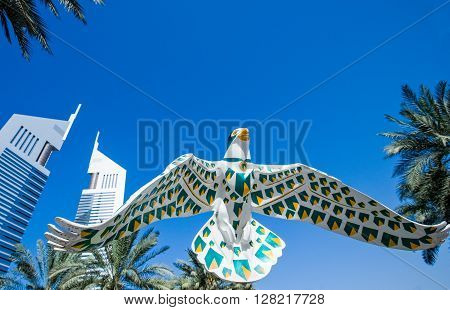 Dubai U.A.E. - February 18 2007: A falcon sculpture between the architectures of the business area of the Sheik Zaied Road. In the background The Emirates Towers.