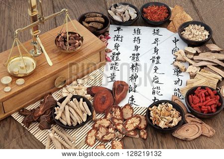 Chinese herbal medicine with herbs, scales and calligraphy. Translation reads as, chinese herbal medicine as increasing the bodys ability to maintain body and spirit health and balance energy.
