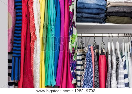 Fashion clothes in walk-in clothing closet or store display for shopping display. Colorful choices of trendy outfits well arranged in clean racks. Spring cleaning concept. Summer home living wardrobe. poster
