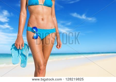 Sexy beach bikini beautiful woman relaxing sunbathing on tropical vacation holding flip flops sandals and sunglasses essentials accessories. Abs stomach body and legs crop. Suntan skin body care.
