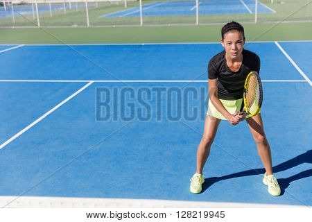 Asian tennis player woman ready to play on blue hard court outdoor in summer in position holding racket wearing outfit with skirt and shoes. Female athlete determination and concentration concept.