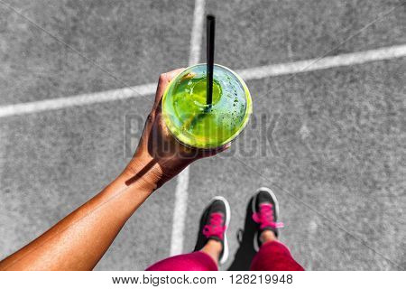 Green smoothie woman drinking plastic cup breakfast meal takeaway to go after morning run on city streets. Healthy lifestyle sporty person pov of hand holding glass with running shoes feet selfie.