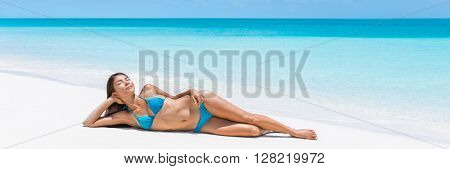 Caribbean turquoise ocean getaway beach destination lady dreaming on perfect white sand. Paradise tropical travel destination. Asian blue bikini woman lying down relaxing sun tanning laid back.