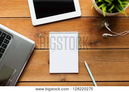 education, business and technology concept - close up of notebook with on laptop computer and tablet pc on wooden table